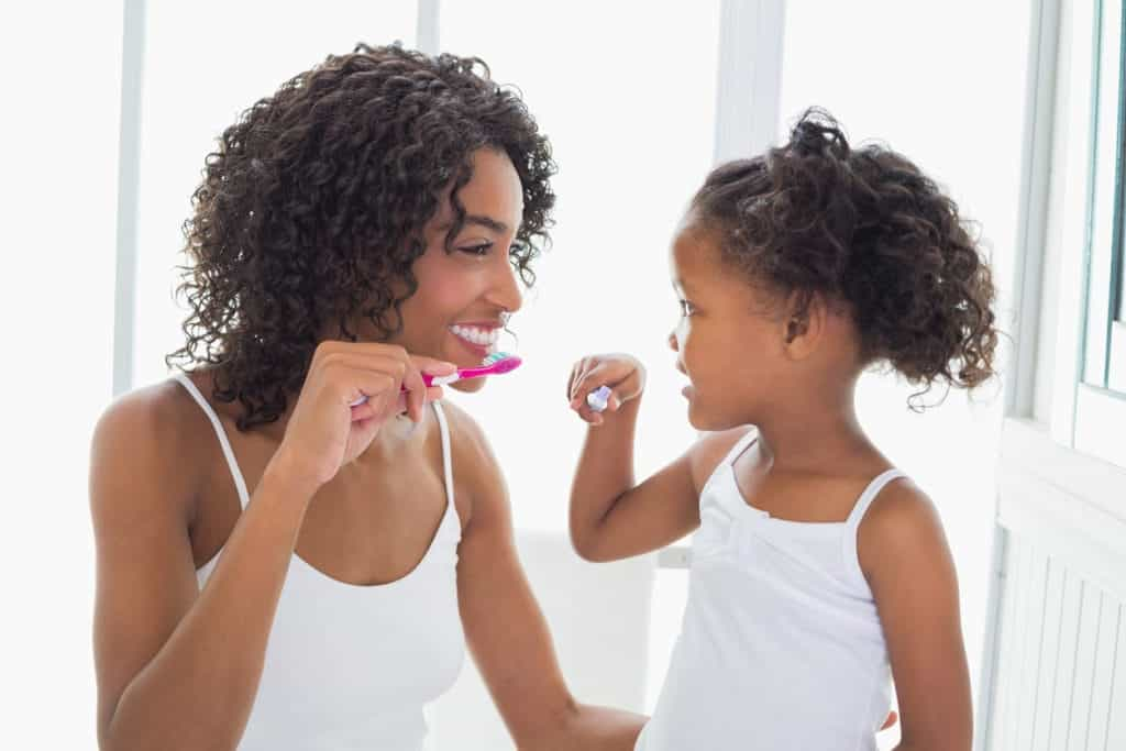 Mother Teaching Daughter To Brush Teeth | Burt's Pharmacy and Compounding Lab